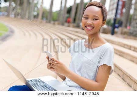 cheerful afro american college student texting on her cell phone