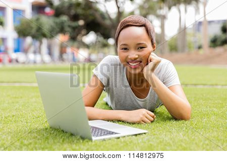 beautiful young woman with laptop computer lying outdoors