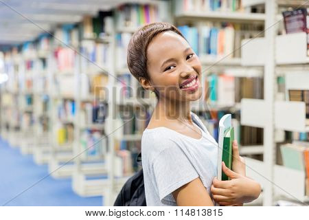 attractive female african college student holding books in library