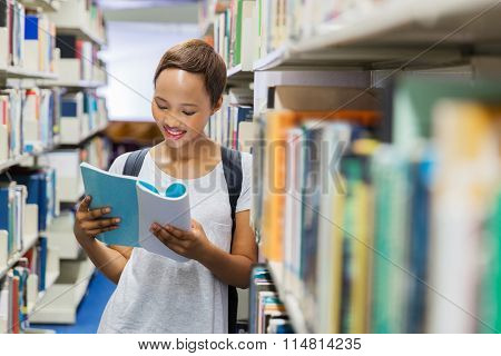 smiling young black student reading a book in university library