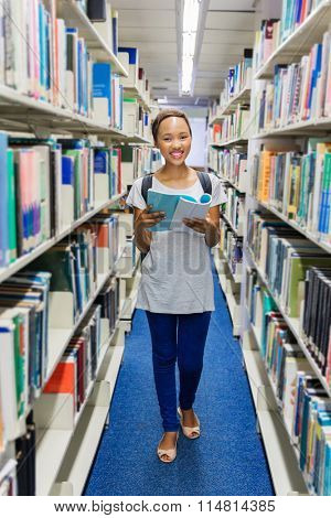 african university student in library reading a book
