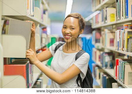 pretty african college girl looking for book in school library