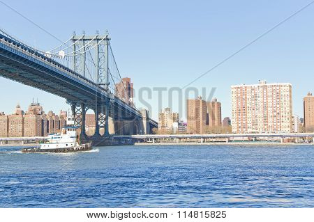 Boat Passing Below Manhattan Bridge At New York
