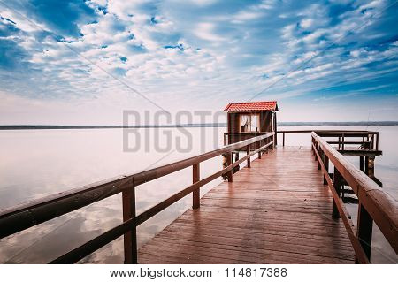 Beautiful wooden pier for fishing, small wooden house shed and b