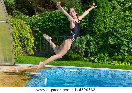 Happy active child jumps to swimming pool. Beautiful smiling girl having fun on summer vacation