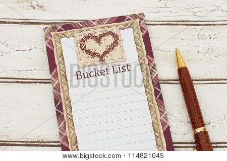A Notepad And Pen On Weathered Wood Background With Text Bucket List And Copy-space