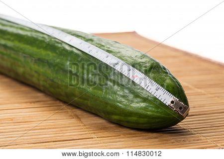Closeup With A Big Cucumber And A Centimeter.