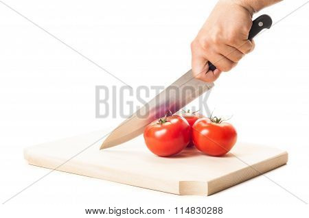 Hand Holding A Big Knife, Three Tomatoes And Wooden Board.