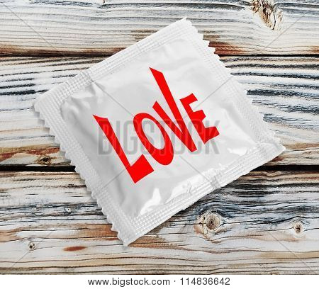 Condom with text Love on wooden table