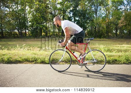 Young Bearded Hipster Driving Fast Bicycle