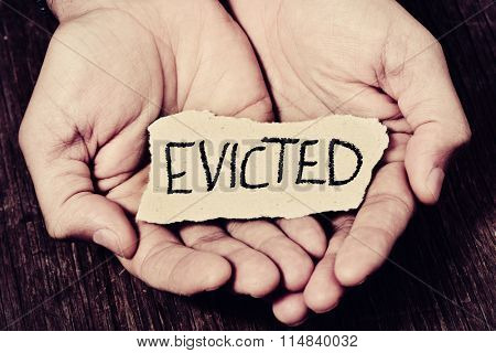 closeup of a piece of paper with the word evicted in the hands of a caucasian man