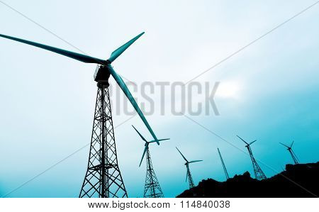 some wind turbines in a wind farm, in a cloudy day