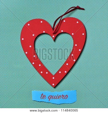 a heart-shaped ornament and the text te quiero, I love you in Spanish, on a colorful blue dot-patterned background