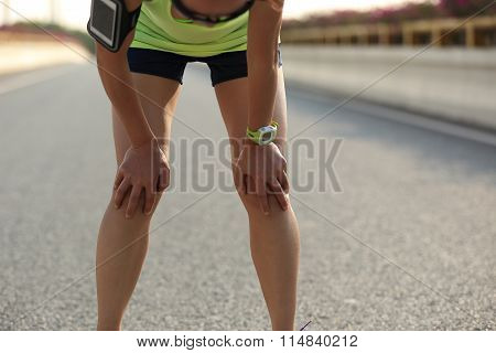 tired young woman runner taking a short break on road