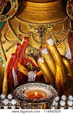 Maitreya Buddha hands with burning lampion in Thiksey Gompa. Ladakh, India