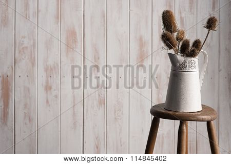 Wide-angle Of Vase With Thistles On Stool Over Wooden Backdrop