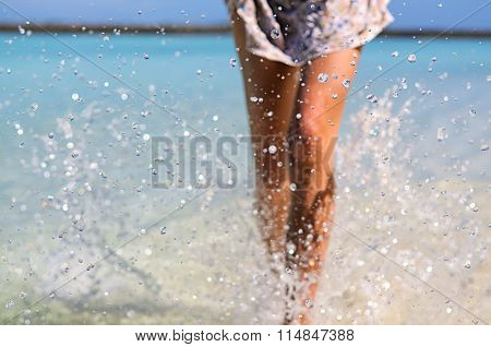 Young Slim Fit Tanning Woman Making Water Splash With Her Sexy Legs. Vacation And Summer Mood