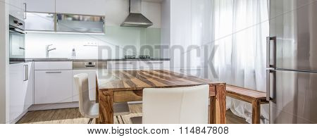 Modern Kitchen Interior Design Architecture Stock Image, Photo of a modern white kitchen with a dark wood table, hi-end appliances and plenty of daylight (panoramic photo)