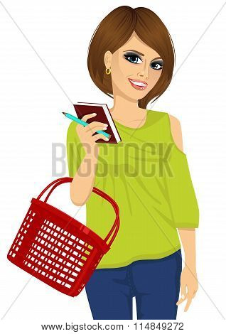 attractive woman holding notebook with pen and shopping basket