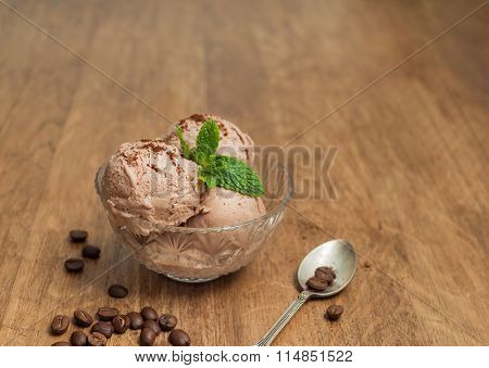 Coffee ice cream in glass bowl on wooden background