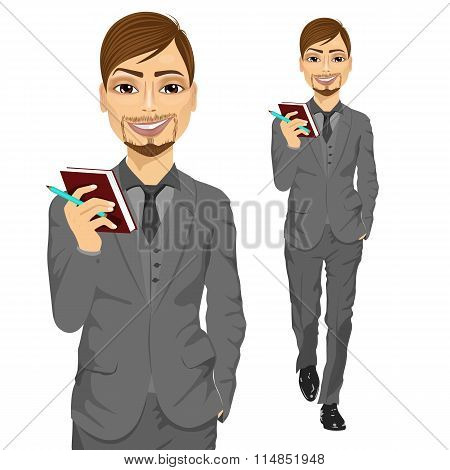 handsome business man holding notebook and a pen walking forward