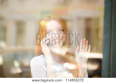 Portrait of a smiling redhead woman talking on the phone and waving palm to somebody