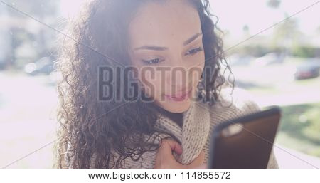 Cute Young Latino Woman Looking At A Cell Phone Device