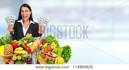 Happy young woman with grocery shopping cart and American dollars.