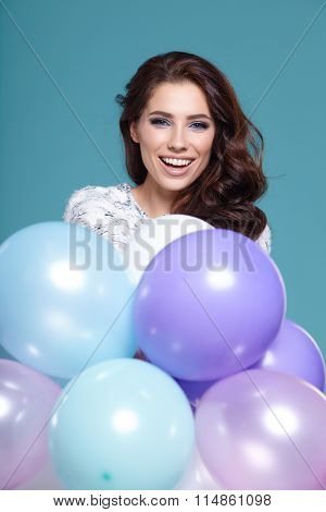 Happy young woman with colorful latex balloons,