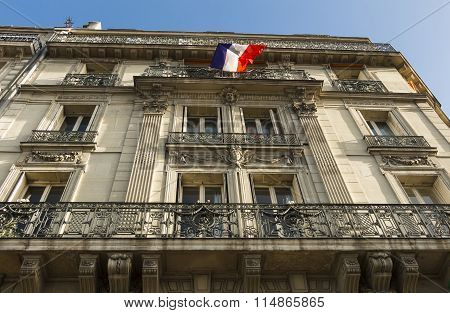 Traditional Parisian  House With Balconies And Exposed French Flag.
