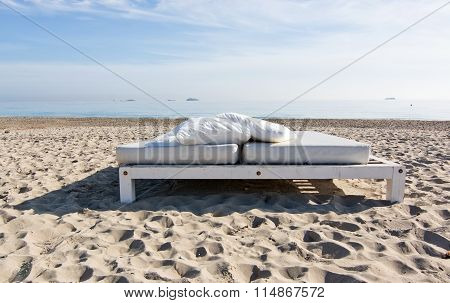 White Sunbeds On The Sandy Playa D'en Bossa Beach