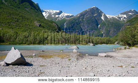 Norway. The Stream Of Blue Water From A Glacier Flows Between The Mountains Lit With The Sun