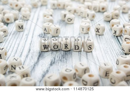 Word made with block wood letter next to a pile of other letters over the wooden board surface compo