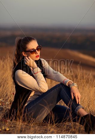 Fashionable, beautiful, glamour, stylish, sexy, young, elegant, hot, sunny, nice, colorful girl with wonderful sunglasses, black vest outdoors on the hill with a beautiful look in the summer, good time, sex, sunny