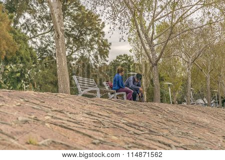 Adult Couple Sitting At Park In Montevideo, Uruguay