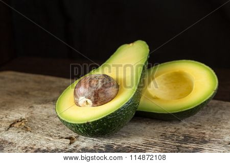 Halved Avocado On Old Wooden Board