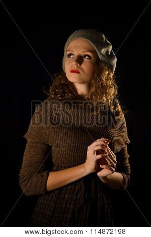 The portrait of notable, caucasian, self-assured, proud, well-mannered, fashionable, glamorous pretty, important, parisian, french, colorful with good manners girl, model in a gray beret on the black background