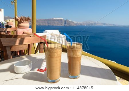 Ice coffee frape at balcony view on caldera