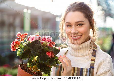 Cheerful beautiful woman florist holding flowering begonia in garden center