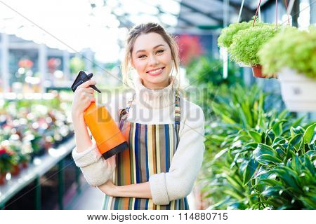 Cheerful attractive young woman gardener in colorful striped apron standing in orangery and holding water pulverizer