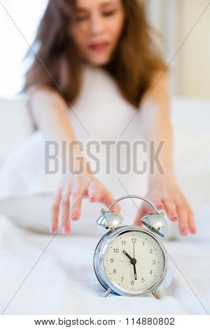 Young sleepy woman trying to turn off the alarm clock. Focus on alarm