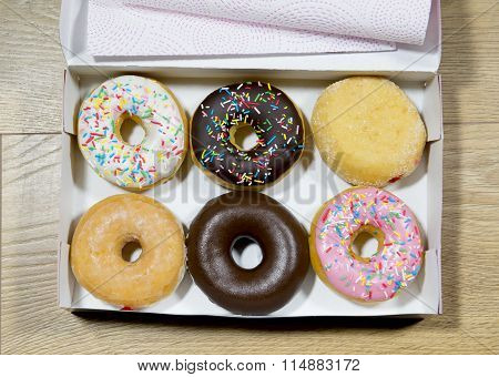 Opened Box With A Donut Set In Various Flavors Such As Chocolate Strawberry Cream And Candy Toppings