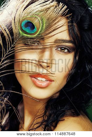 young sensitive brunette woman with peacock feather eyes close up on green smiling