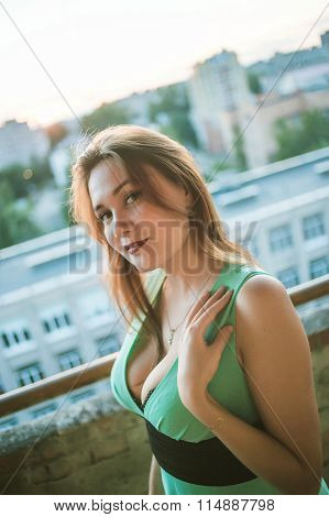 Young beautiful busty girl in the green dress with an open neckline  and expressive make up on city