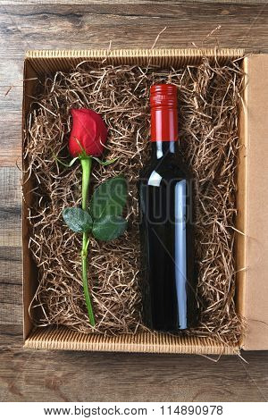 A single red rose and a bottle of wine in a cardboard box filled with packing material. High angle shot. Valentines / Love / Romance Concept.