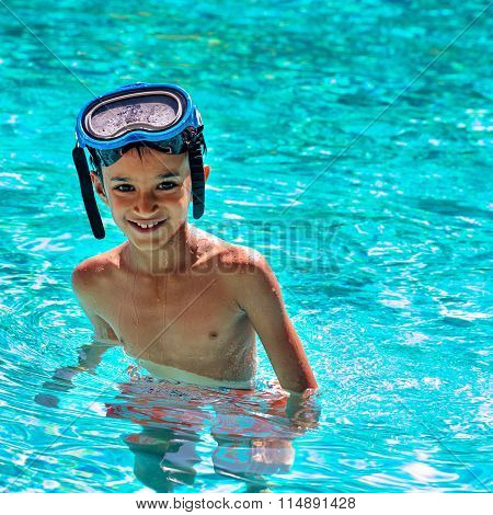 Boy eight years old inside swimming pool portrait happy fun bright day diving goggles squa