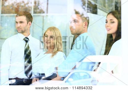 Happy smiling business team looking through window