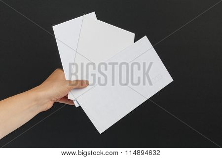 Female Hand Delivering 3 Envelopes On Black Background