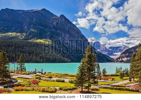 Banff National Park, Rocky Mountains, Canada. Flowers on the embankment of glacial Lake Louise.  Emerald Lake is surrounded by mountains, glaciers and pine forests
