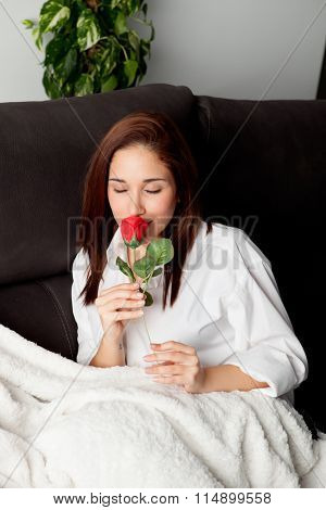 Excited young woman with a red rose on her couch